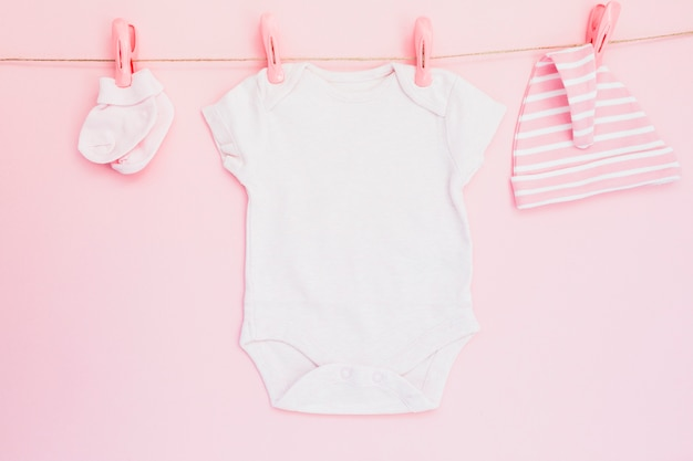 Baby clothes hanging on pink Free Photo