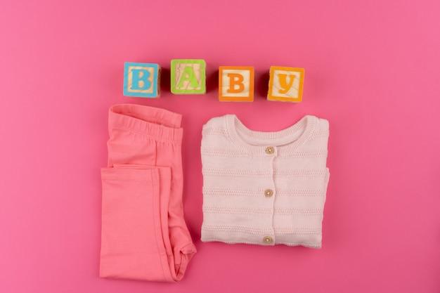 ピンクの背景の上面にベビー服 Premium写真