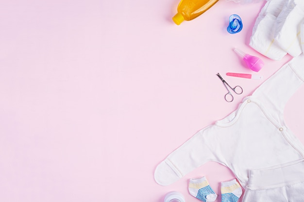 Baby clothes and other stuff for child on pink background. newborn baby concept. top view Premium Photo