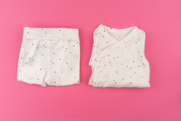Baby clothes on pink background top view   Premium Photo