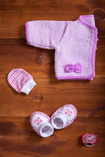 Детская одежда розовый вязаный свитер варежки носки и манекен на деревянный стол Premium Фотографии