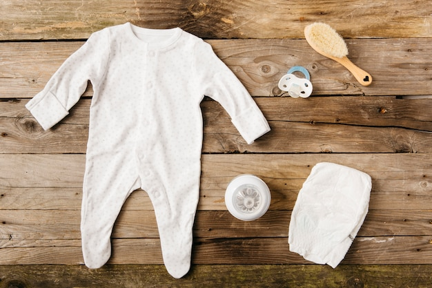 Baby clothing; milk bottle; pacifier; brush and diaper on wooden table Free Photo