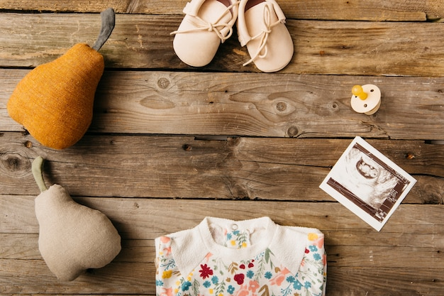 Baby clothing; shoes; pacifier; ultrasound picture and stuffed pear on wooden table Free Photo