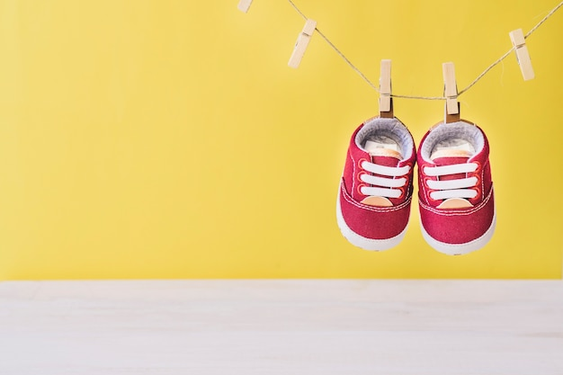 Baby concept with shoes on clothesline Free Photo