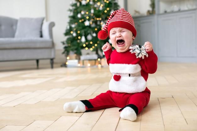 Baby in cristmas costume crying on floor Premium Photo