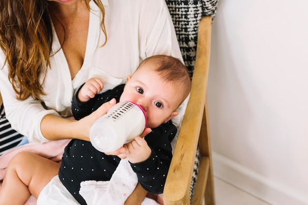 Baby drinking milk from bottle Free Photo