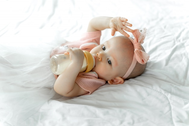 Baby drinks milk from a bottle on a white bed Free Photo