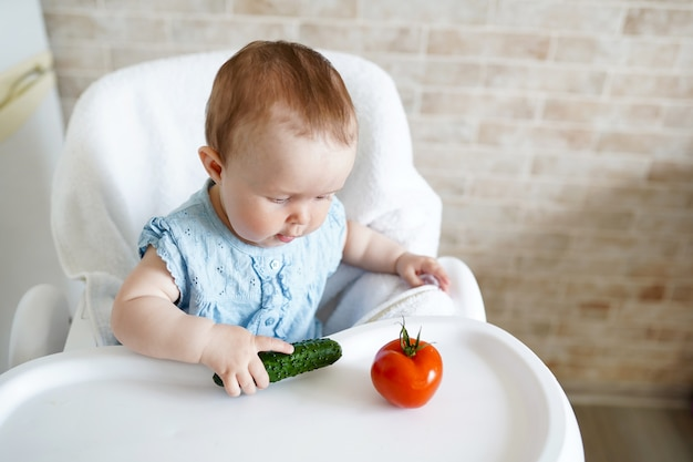 Baby eating vegetables. green cucumber in little girl hand in sunny kitchen. Premium Photo