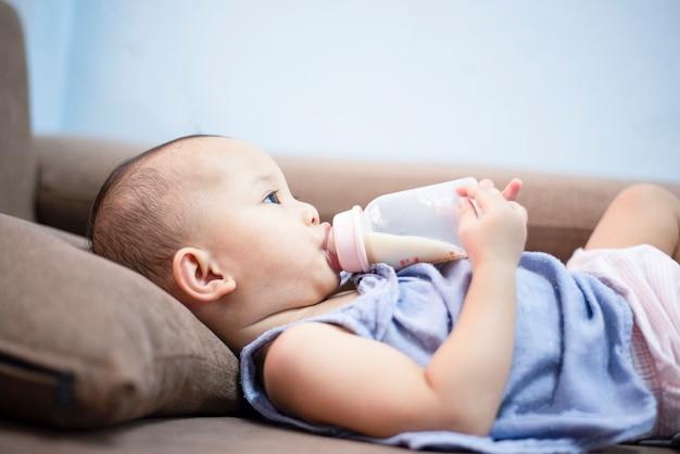 Baby feeding bottle - closeup portrait of asia child hold milk bottle and feeding on sofa bed Premium Photo