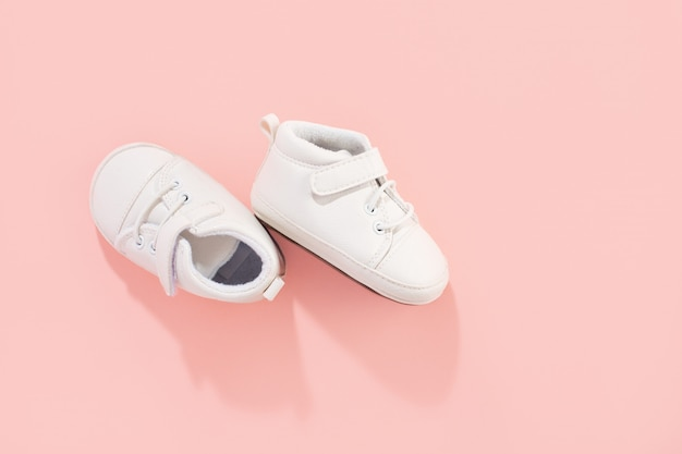 パステル調のピンクの背景の赤ちゃんの最初の靴。家族や母性の概念。 無料写真