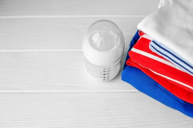 Детское питание в пластиковой бутылке и стопке одежды Premium Фотографии