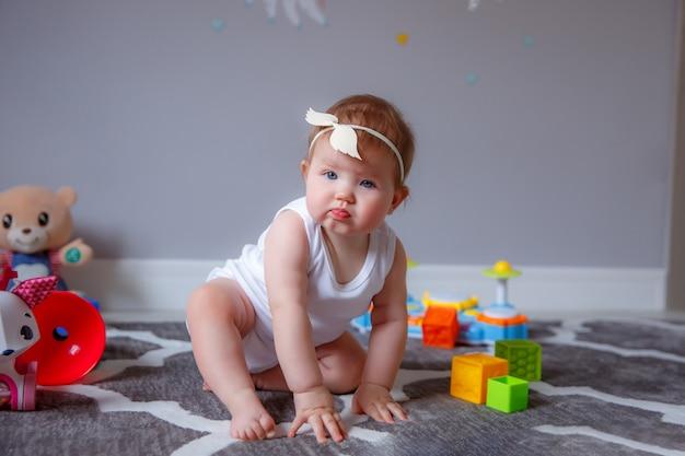 おもちゃで遊んで床に座って家で女の赤ちゃん Premium写真