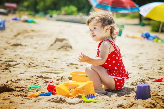 Baby girl on the beach, by the sea. selective focus. Premium Photo