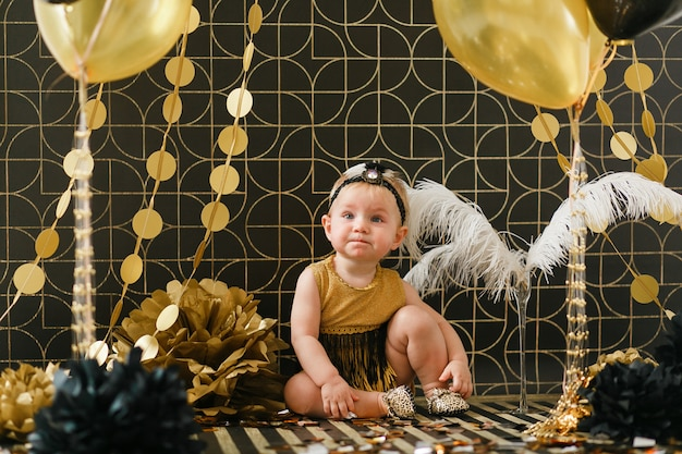Baby girl birthday party decorated with black and golden balloon. Free Photo