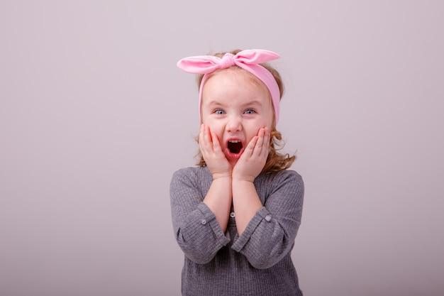 Девочка блондинка показывает разные эмоции удивление, радость Premium Фотографии