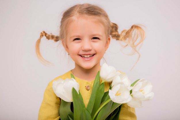 Baby girl blonde with a bouquet of tulips on a light background Premium Photo