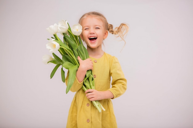 Baby girl blonde with a bouquet of tulips on a light background. Premium Photo