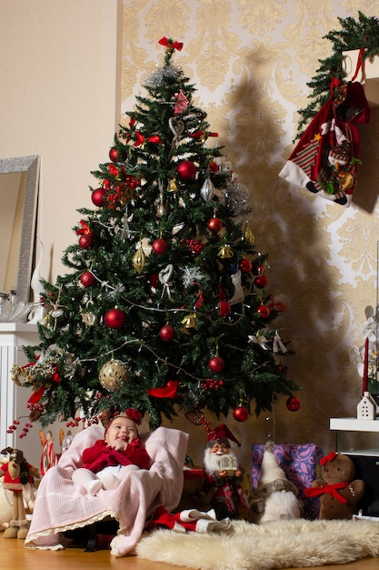 Baby girl under christmas tree with stuffed toys Free Photo