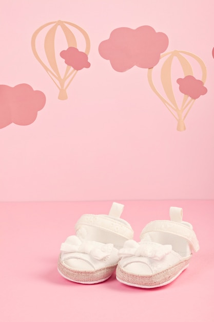 Baby girl cute pink shoes over the pink pastel background with clouds and ballons Premium Photo
