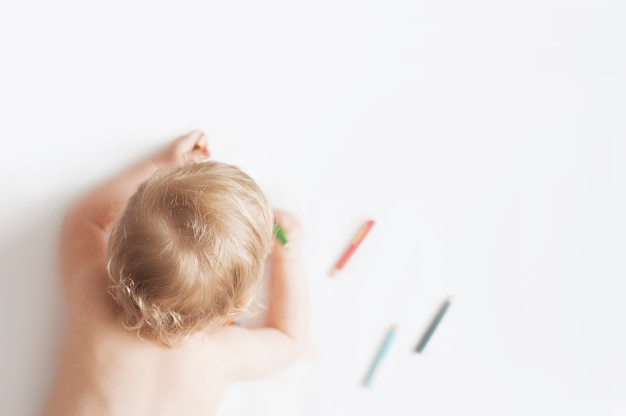 Baby girl drawing with colorful pencils on white background Premium Photo