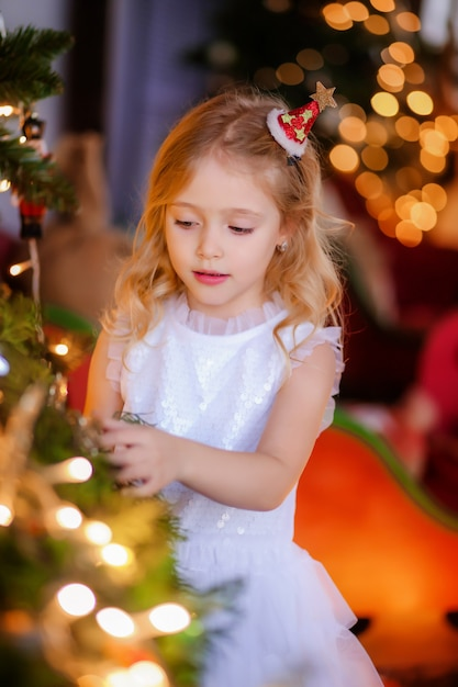 Baby girl dresses up a christmas tree Premium Photo