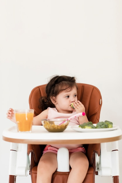 Baby girl eating in a child chair Free Photo