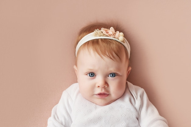 Baby girl of four months lies on a light pink wall Premium Photo