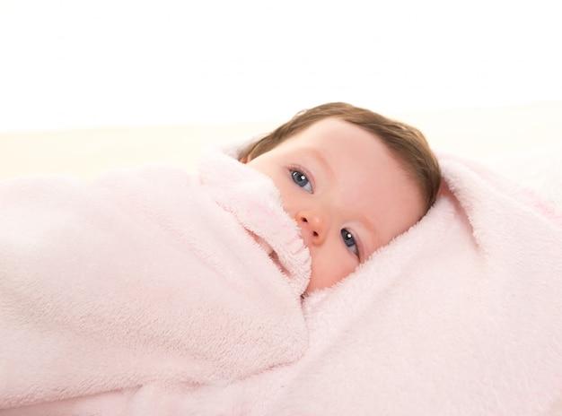Baby girl under hidden pink blanket on white fur Premium Photo
