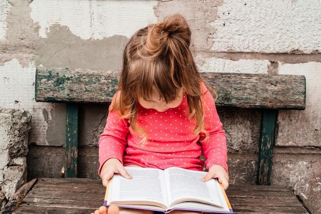 緑の草の上に赤で、晴れた夏の日に本を読んでいる女の赤ちゃん。 Premium写真