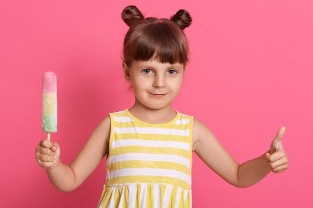 Bambina bambino mangia il gelato, sembra felice e mostra il pollice in su Foto Gratuite