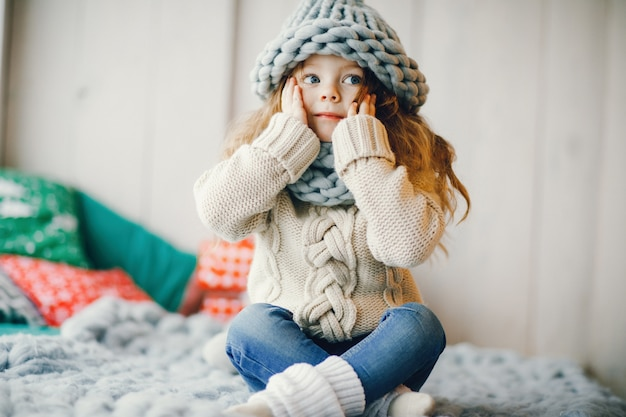 Baby girl in knitted hat and scarf Free Photo