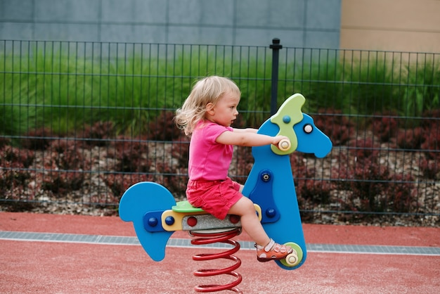 Девочка на детской площадке, верховая езда Premium Фотографии