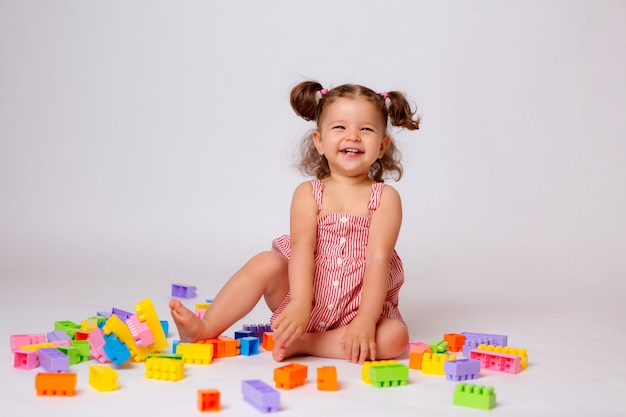 Baby girl playing with multicolored constructor Premium Photo