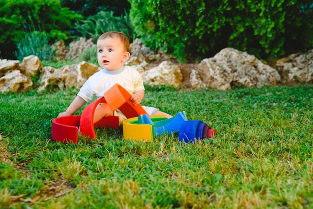 Baby girl playing with a waldorf material, a rainbow of wood montessori, in nature. Premium Photo