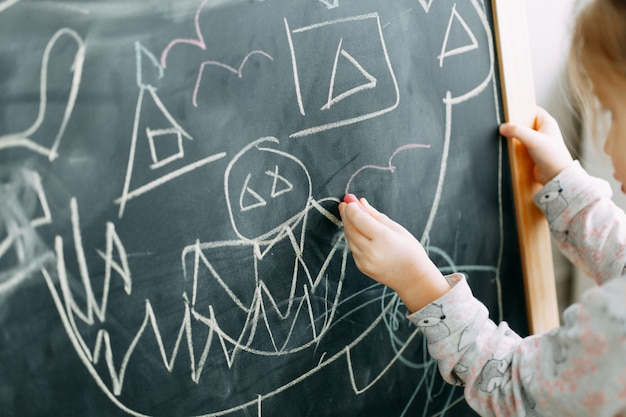 Baby girl pupil draws a funny monster with chalk on a black blackboard Premium Photo