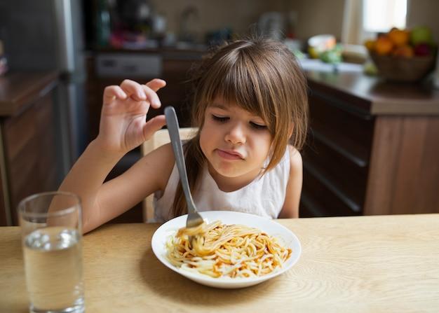 Baby girl refusing pasta dish at home Free Photo
