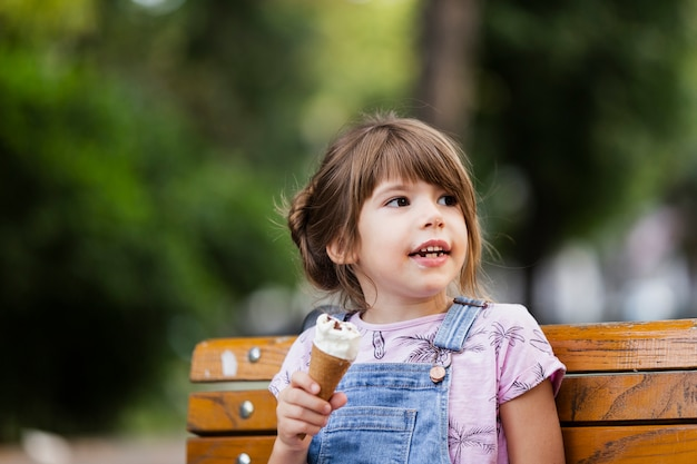 Baby girl sitting on bench while eating ice cream Free Photo