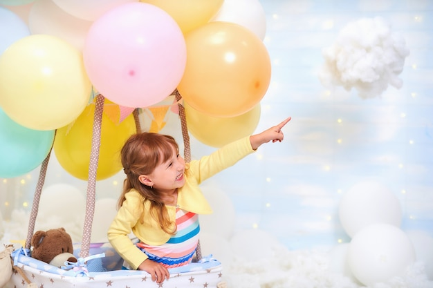 Baby girl sitting on a cloud next to a basket of balloon in the clouds Premium Photo