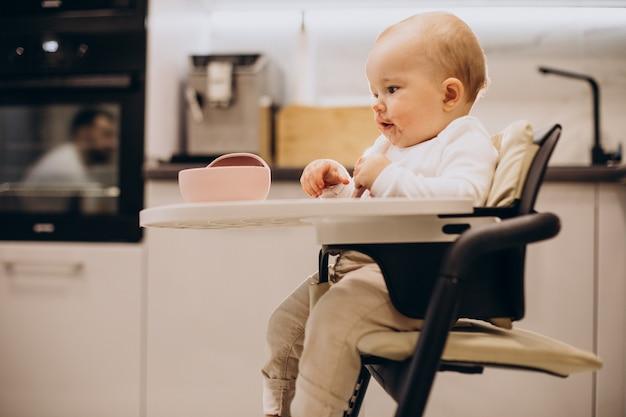 아기 소녀 의자에 앉아 식사 무료 사진