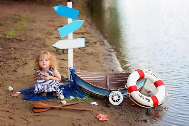Девочка сидит на пляже возле лодки Premium Фотографии