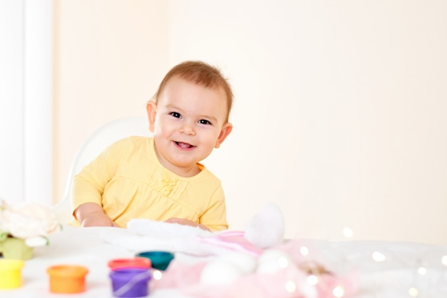 Baby girl sitting at the table and painting holiday easter eggs smiling happy childhood Premium Photo