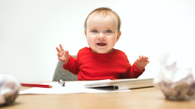 一杯のコーヒーとキーボードで座っている女の赤ちゃん 無料写真