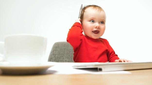 ペンとキーボードで座っている女の赤ちゃん 無料写真