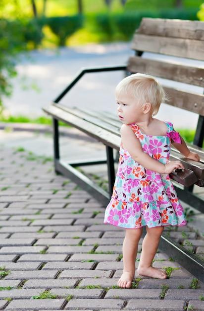 ベンチの近くに立っている女の赤ちゃん Premium写真