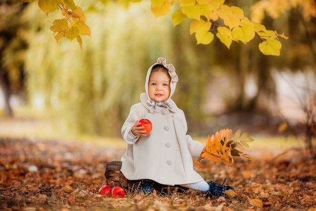 Baby girl on a walk in the autumn park Premium Photo