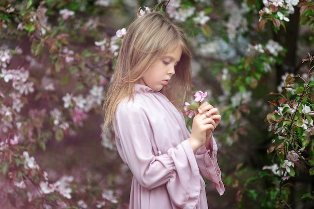 Девочка с цветком во время сезона цветения яблони. Premium Фотографии