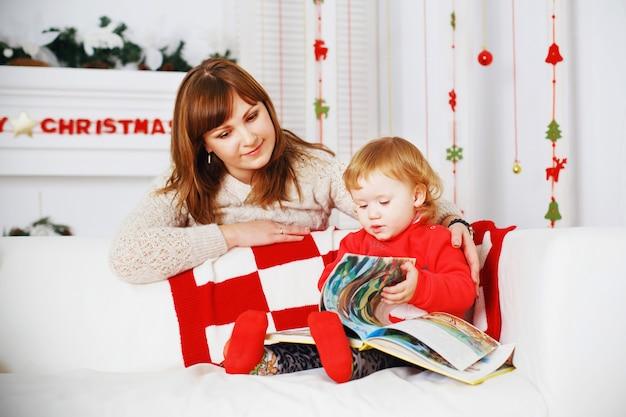 彼女の母親と一緒に女の赤ちゃんは、新年の装飾が施されたインテリアで本を読みます Premium写真