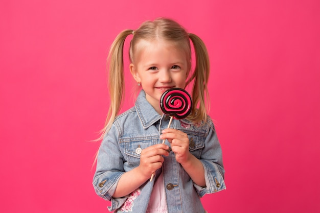 Baby girl with lollipop on pink background Premium Photo