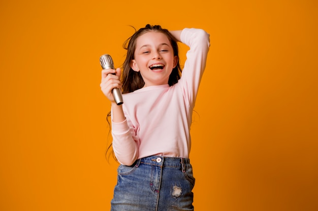 Baby girl with microphone smiling singing Premium Photo