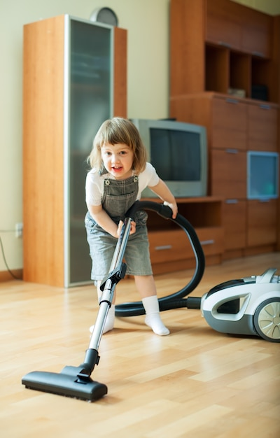 Baby girl with vacuum cleaner Free Photo